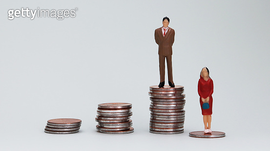 Gender wage difference concept. A miniature man and a woman standing on top of a pile of coins.