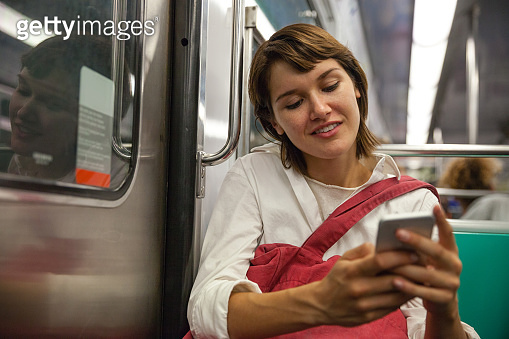 Young woman commuting by train subway in Paris using mobile while waiting