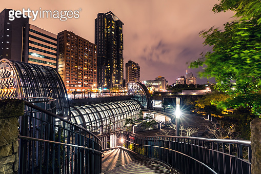 Taiwan - Taipei: entrance of the subway station and financial district buildings at night at Daan Park