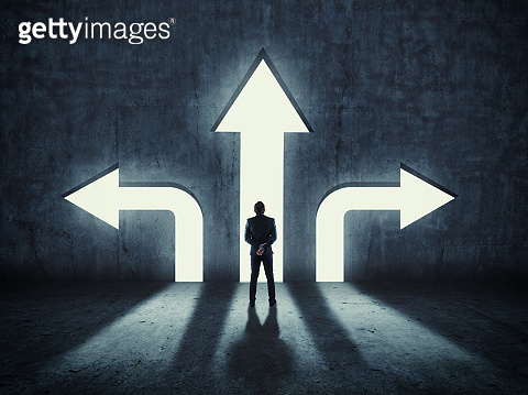 Businessman having to choose between three different arrows pointing in opposite direction. The concept of hard choice.