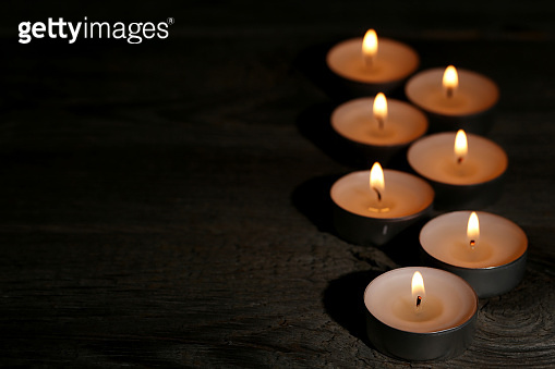 White burning candles on black background