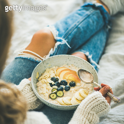 Woman in jeans and sweater eating vegan breakfast, square crop