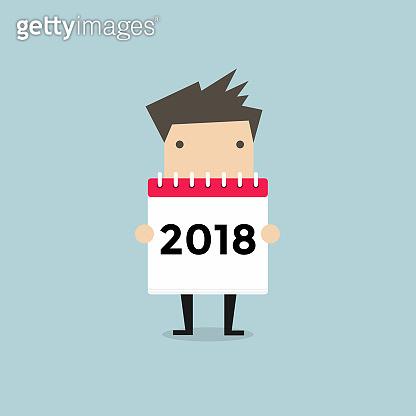 Businessman hold a calendar 2018 on his hand.