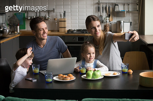 Happy family with children taking selfie on phone having breakfast