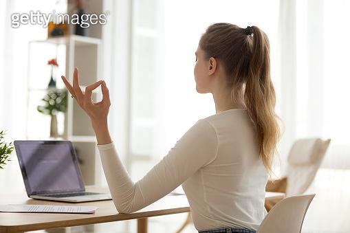 Focused female practice yoga at home desk