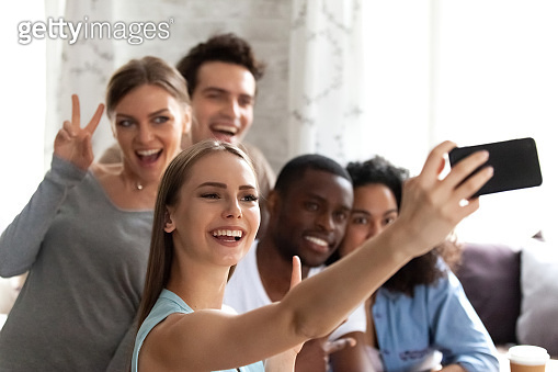Female holds smartphone making selfie photo with multiracial friends