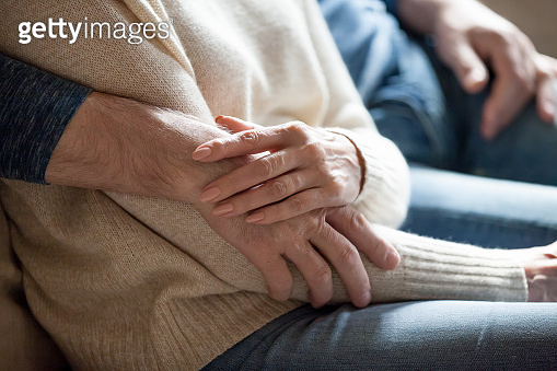 Close up of senior romantic couple hug at home couch