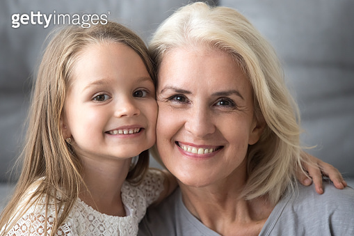 Happy old grandmother hugging smiling grandchild looking at camera