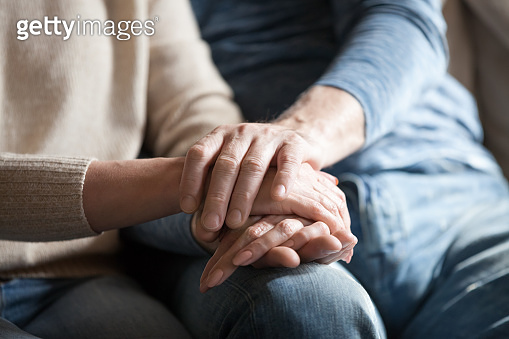 Closeup view of mature couple holding hands giving psychological support