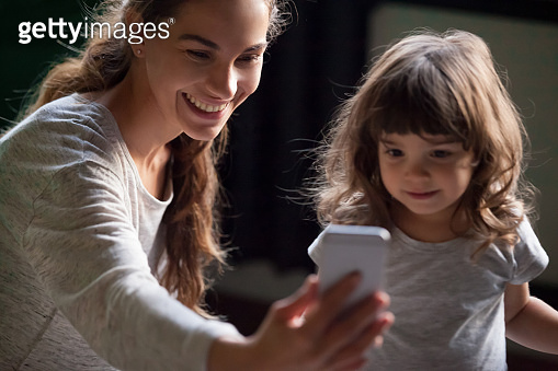 Smiling mother taking selfie with kid daughter on smartphone