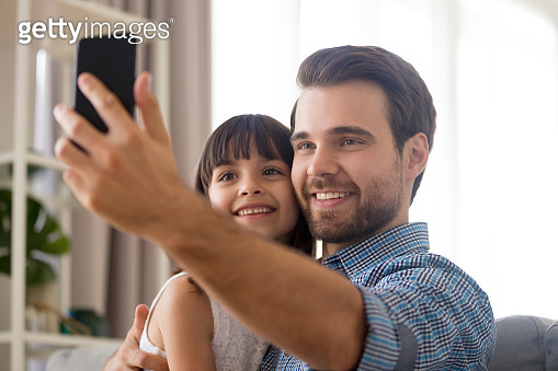 Father and daughter using smartphone take selfie photography