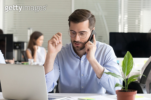 Sales manager consulting client talking on phone in office