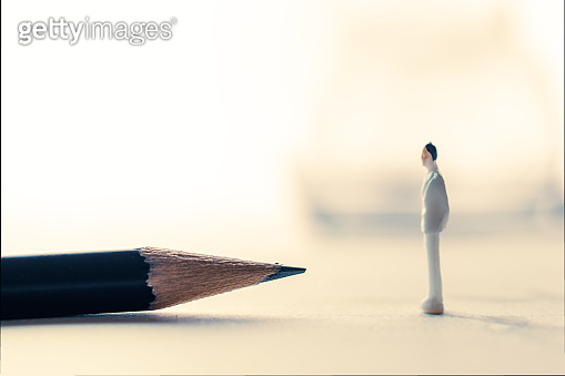 Miniature people with close up pencil thinking concept.