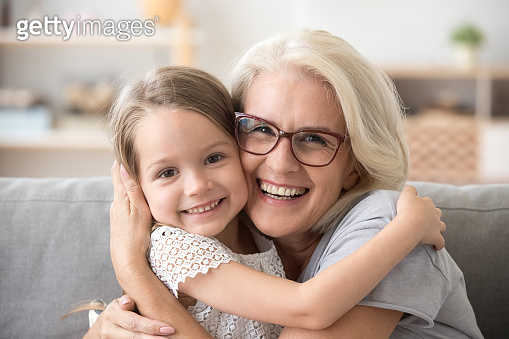 Happy older grandmother hugging little grandchild girl looking at camera