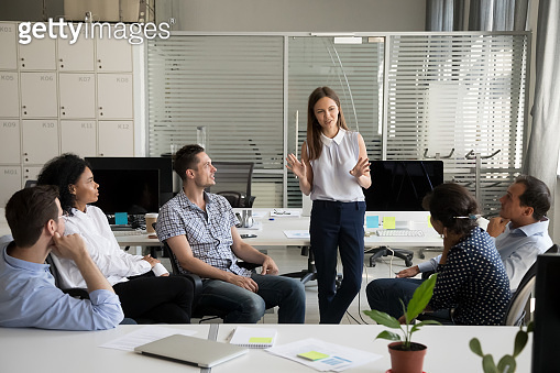 Friendly young female worker speaking at diverse corporate group meeting