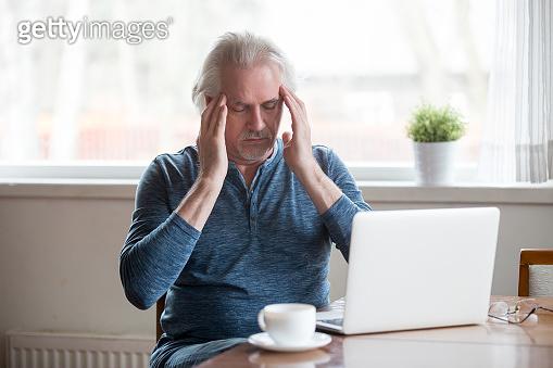 Tired senior man touching temples feeling headache working on laptop