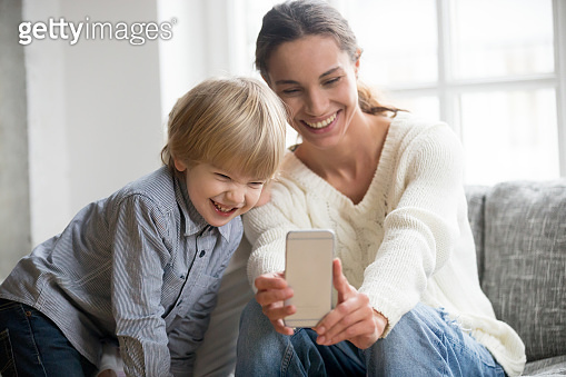Happy mother laughing taking selfie with little son on smartphone