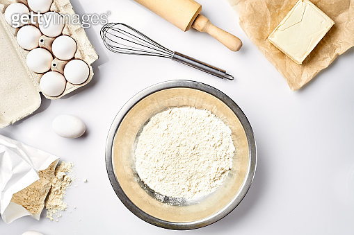 Preparation of the dough. A measurement of the amount of ingredients in the recipe. Ingredients for the dough: flour, eggs, rolling pin, whisk, butter. Top view, space for text