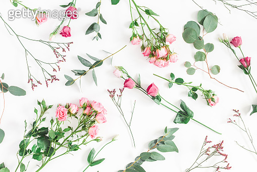 Pink flowers and eucalyptus branches. Flat lay, top view