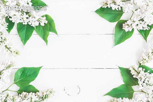 White lilac flowers on wooden background. Flat lay, top view