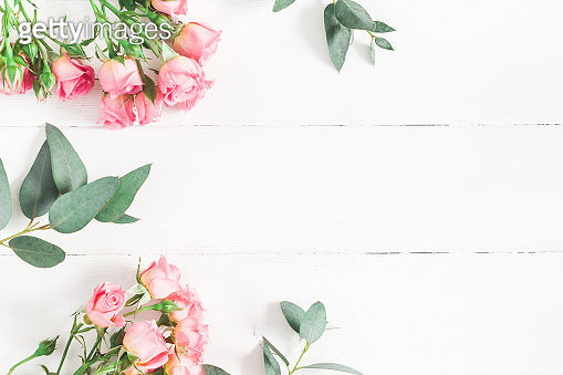 Eucalyptus branches and pink rose flowers. Flat lay, top view