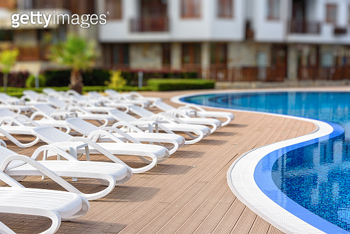 White loungers near the swimming pool at summer