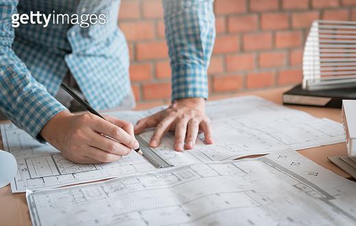 Engineering man standing examining working on blueprint.