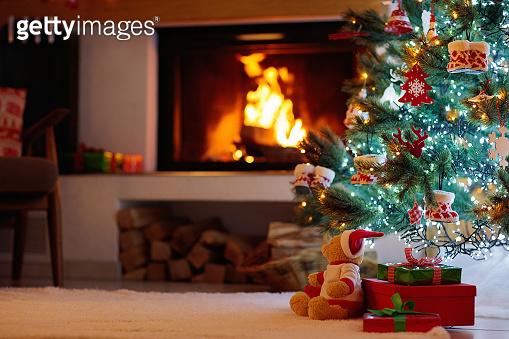 Christmas tree with presents at fire place.