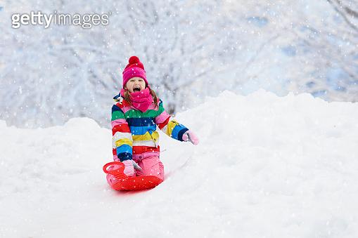 Girl on sled ride. Child sledding. Kid on sledge