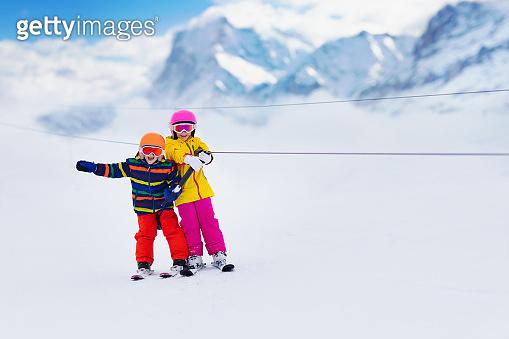 Child on ski lift. Kids skiing.
