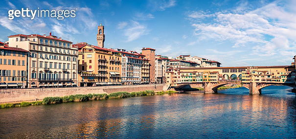 Sunny spring cityscape of Florence with Old Palace (Palazzo Vecchio or Palazzo della Signoria) on background and Ponte Vecchio bridge over Arno river. Colorful morning scene in Italy, Europe.