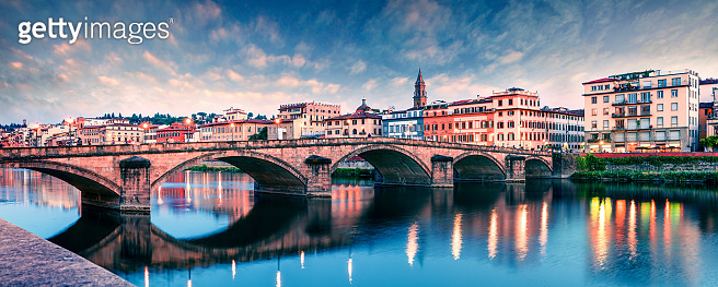 Picturesque medieval arched Ponte alla Carraia bridge over Arno river. Colorful spring sunset in Florence, Italy, Europe. Traveling concept background.
