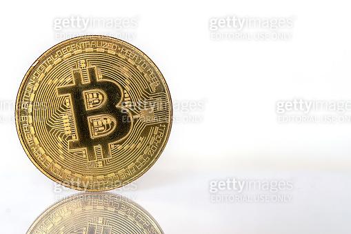 A single bitcoin sitting on a reflective surface and white background