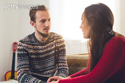 Couple talking seriously at home