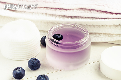 Blueberry extract skincare moisturizer in glass jar with fresh berries, white towels, soft light.