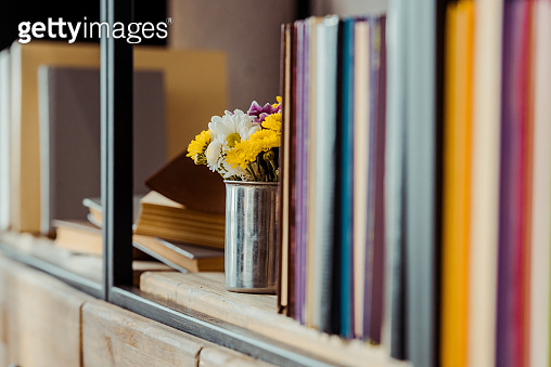 close up of bookshelf  with flowers in can and books