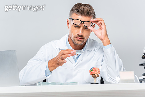 surface level of handsome scientist looking at reagent at table isolated on white