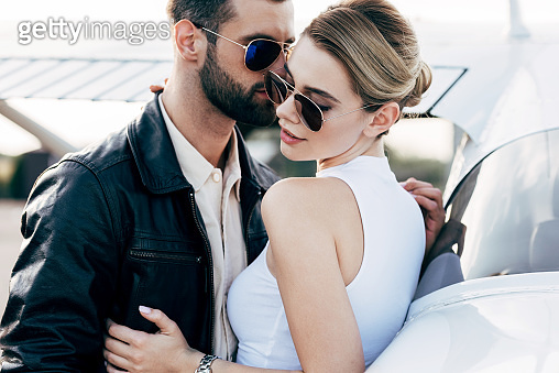 stylish man in leather jacket and sunglasses embracing attractive girlfriend near plane
