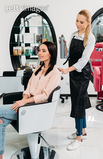 hairdresser looking at new hairdo of customer