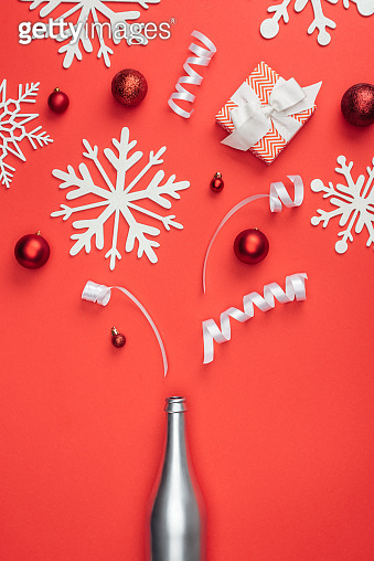 top view of present, silver bottle, red christmas toys, white ribbons and decorative snowflakes arranged isolated on red
