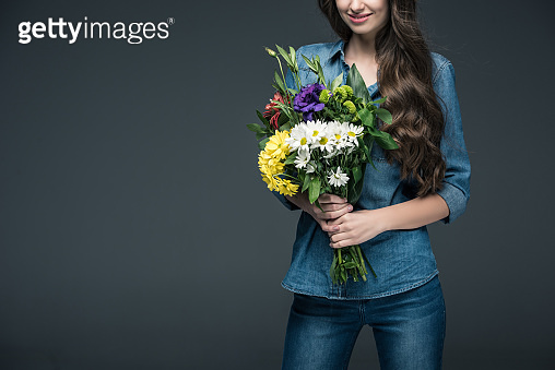 cropped view of girl in denim clothes holding bouquet of flowers for international womens day, isolated on grey