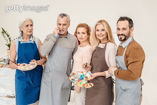 senior and mature artists in aprons smiling at camera at art class