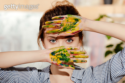 beautiful young artist with palms in paint looking at camera