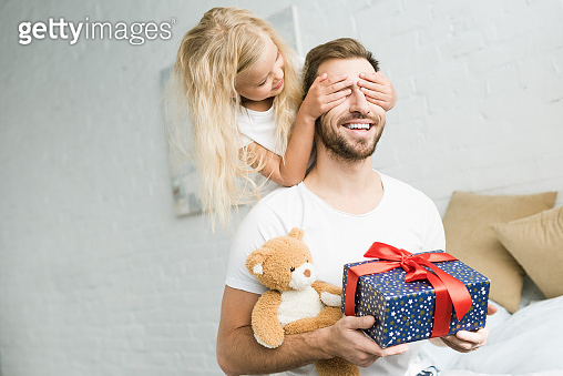 cute little daughter closing eyes to happy father holding gift box and teddy bear