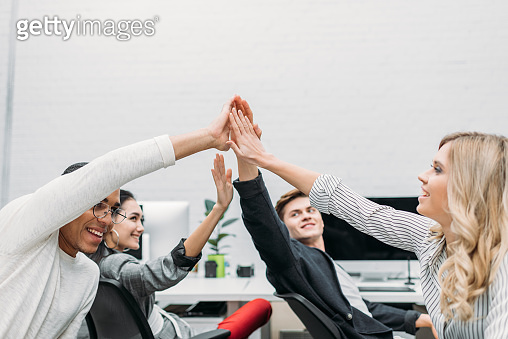group of multiethnic business partners giving high five