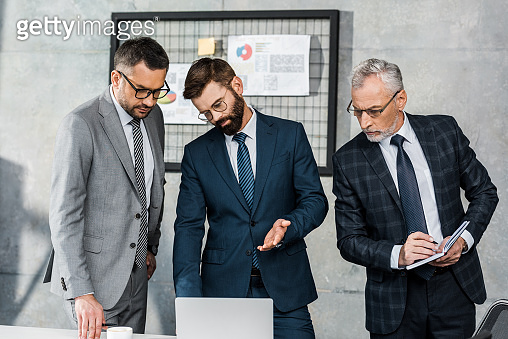 three serious professional businessmen looking at laptop and discussing project in office