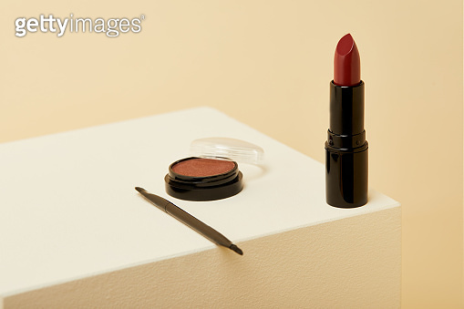 close-up shot of lipstick standing on beige surface with can of blush and brush