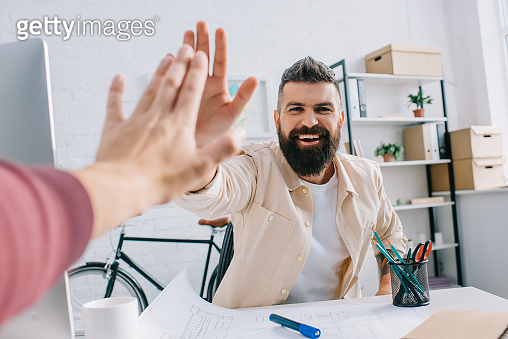 Smiling architect giving high five to coworker at modern office