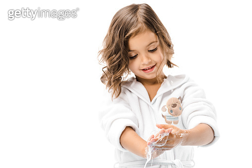 portrait of little kid in bathrobe washing hands with soap isolated on white