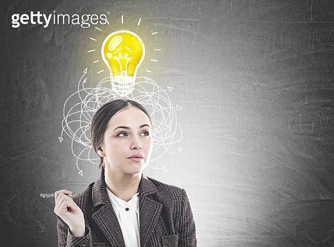 Pensive businesswoman with a pen, idea concept